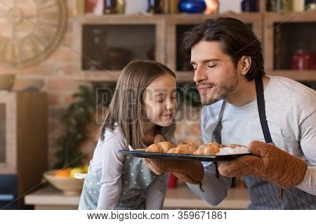 Homemade Pastries. Cute Little Girl And Her Dad Holding Tray And Smelling Freshly Baked Croissants,