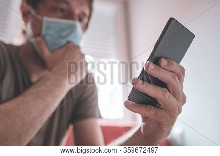 Worried Man Using Mobile Phone In Home Quarantine Self-isolation For Having Covid-19 Coronavirus Sym