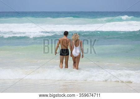 Beautiful Lover Couple Enjoy Their Honeymoon Vacation At Tropical Beach, Weaving Ocean In Seychelles