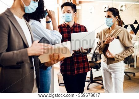 Office Workers In Medical Face Masks Working On Project