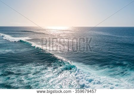Aerial View Of A Surfer Riding A Surf At Sunset, Surfer Ride On Waves In Ocean Sunset, Top View