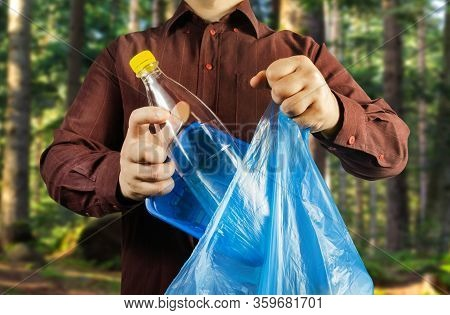 Photo of a man in brown shirt disposing plastic bottle and can in bag protecting forest environtment.