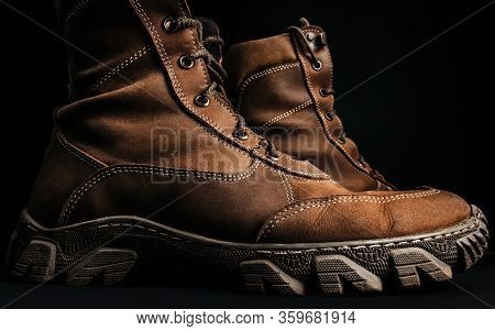 Photo Of Brown Military Tactical Boots Standing On Black Surface Background Profile View.