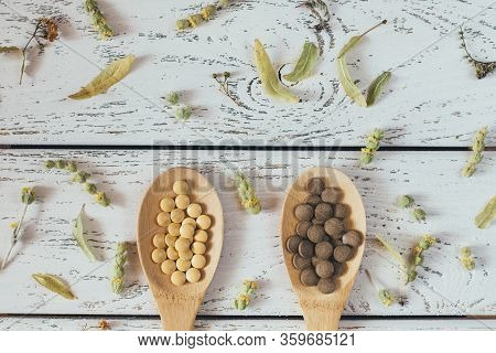 Herbal Homeopathy Natural Pills Or Vitamins In Wooden Spoons And Dry Herbs On White Vintage Backgrou