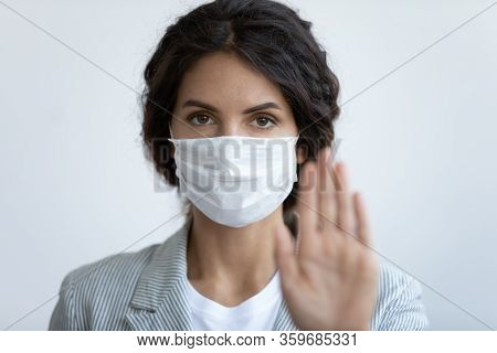 Worried Young Woman In Protective Facemask Showing Stop Sign.