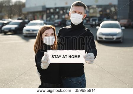 A Woman And A Man In Protective Medical Masks Hold A Placard Reading Stay At Home. Message For Preve