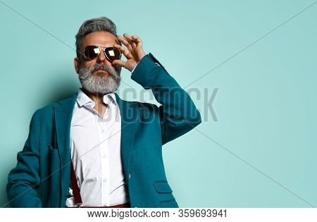 Gray-haired, Bearded Man In White Shirt, Jacket, Brown Pants And Suspenders, Black Loafers. He Strai