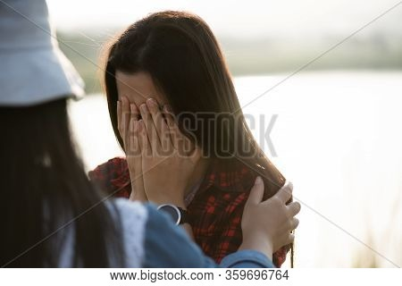 Close Up Of Crying Girl, Who Covers Her Face With Both Hands. Woman Comforting Crying Girl, Comfort