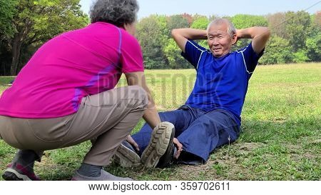 Smiling Senior Grandfather Doing Sit-ups In The Park
