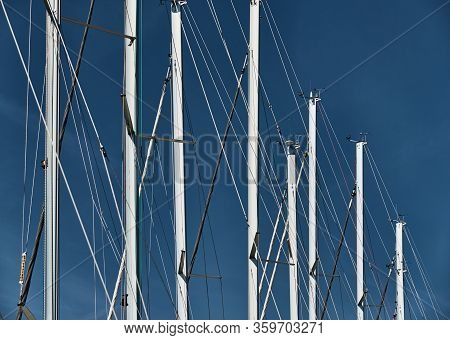 The Number Of Masts Of Sailboats With The Blue Sky On A Background, A Sail Regatta, Reflection Of Ma