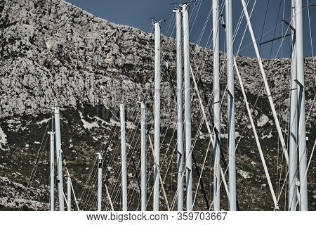 The Number Of Masts Of Sailboats With The Blue Sky And Mountain On A Background, A Sail Regatta, Ref