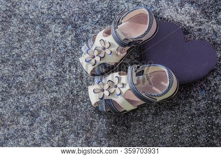 White Childrens Sandals On A Gray-blue Background. Boutique Of Childrens Shoes. White-blue Childrens