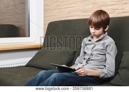 Lonely boy sittng on sofa with tablet computer stuck at home during isolation. Quarantine and lockdown are protective measures against spreading of coronavirus pandemic disease