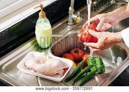 Mature Man Rinsing Vegetables Under Tap Water In Kitchen Sink