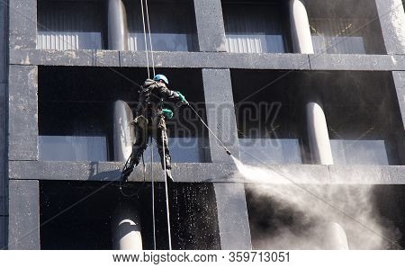 Vancouver, Canada - April 2,2020: Construction Worker Power Washes Windows One Of The Office Buildin