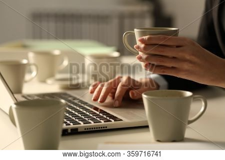 Close Up Of Overworked Executive Woman Hands Working Late Hours Wih Multiple Coffee Cups In The Offi