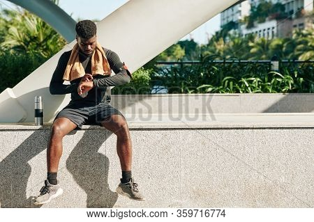 Fit Man Sitting On Stone Parapet After Running And Checking Health Application On His Wrist