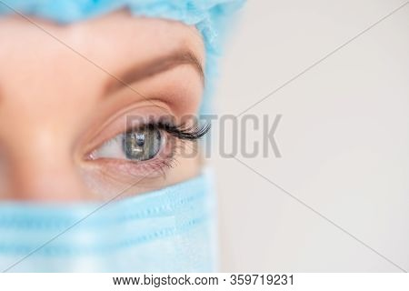 Nurse Or Doctor With Face Mask And Cap. Close Up Portrait Of Young Caucasian Woman Model On White Ba
