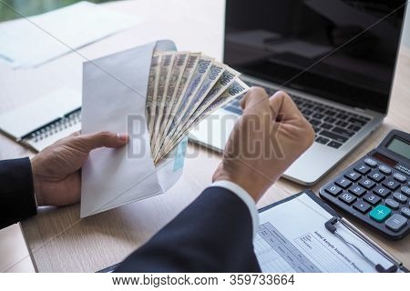 Happy Young Asian Employee Business Man Holding Money Bonus Card In Paper Envelope To Increasing Of