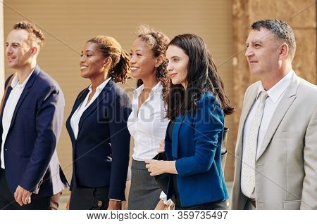 Group Of Positive Ambitious Business People Walking In The Street