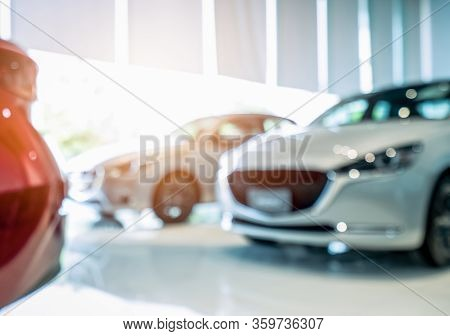Blurred Front View Of White Car. Luxury Car Parked In Modern Showroom. Car Dealership Office. Electr