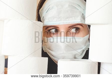 Scared Person In Two Medical Virus Protection Face Masks Looks Through Stacks Of Toilet Paper. Covid
