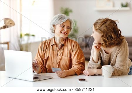 Senior Woman With Credit Card And Laptop Smiling And Looking At Happy Young Granddaughter While Sitt