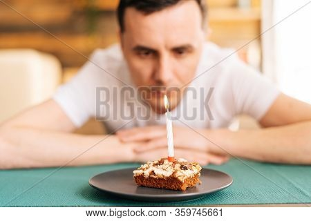 Sad Lonely Young Man In Festive Hat Celebrating Birthday Alone, Sitting At The Birthday Cake And Loo