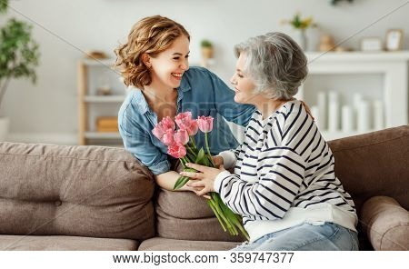 Cheerful Young Female Hugging Happy Aged Mother And Giving Bouquet Of Tulips While Congratulating On