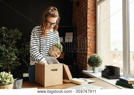 Low Angle Of Satisfied Female Employee In Glasses And Casual Clothes Standing At Wooden Table And Pa