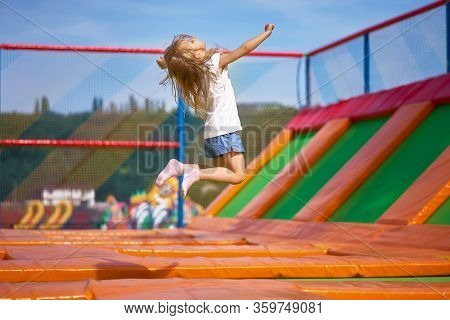 Little Pretty Girl Having Fun Outdoor. Jumping On Trampoline In Children Zone. Happy Girl Jumping On
