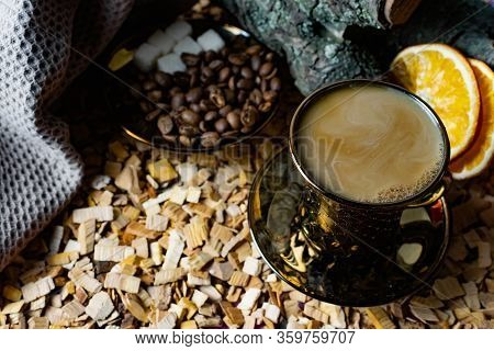Aromatic Dark Coffee, With Milk With Bubbles On The Surface In A Dark Gold Cup On A Saucer, Next To