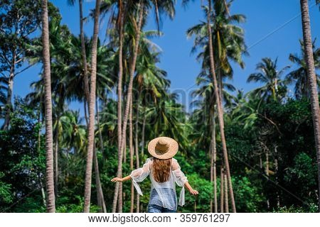 Girl In Straw Against The Background Of Tropical Coconut Trees And Blue Sky. Walk In The Rainforest