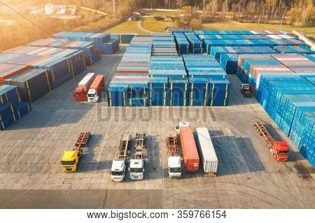 Aerial View Of Trucks And Containers At Sunset. Top View Of Autotrucks, Container Warehouse In Logis