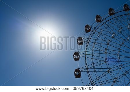 Ferris Wheel On A Background Of Sky And Sun. Ferris Wheel On Sky Background. Ferris Wheel On Sunny S