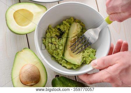 Man Mashing Avocado Flesh With A Spoon