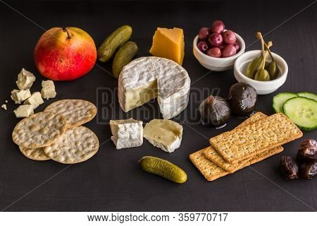 Cheeseboard With Camembert, Cheddar, Crackers, Olives, Figs, Dates And Pickles On Black Texture Back