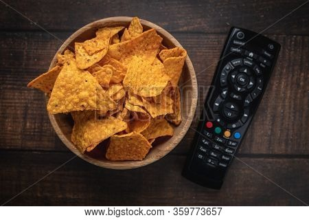 Chips In A Wooden Bowl Next To The Tv Remote Control Against A Burnt Wooden Background. Top View. Cl