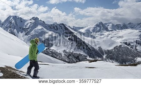 Freerider With Splitboard Or Snowboard For Ski Touring At Winter Mountains Background