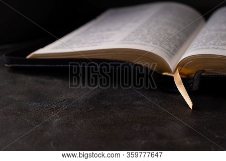 The Holy Bible On Dark Background. Christianity Concept.