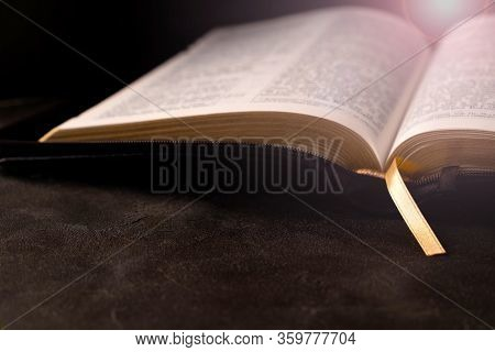 Open Bible On A Dark Table With Light Coming From Above. Christianity Concept. Holy Bible Background