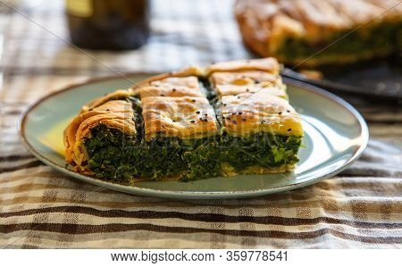 Healthy Food Concept. Spinach Pie Or Greek Spanakopita Serving On Kitchen Table Background, Closeup
