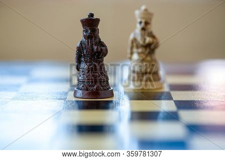 Close-up Of The Black And White King Chess Piece Sitting On A Chessboard. Black Versus White Kings.