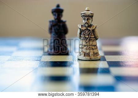 Close-up Of The Black And White King Chess Piece Sitting On A Chessboard. Black King Versus White Ki