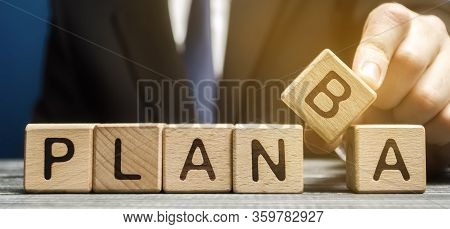 Businessman Chooses Wooden Block With The Words Plan A And B. Strategy Planning. Business Management