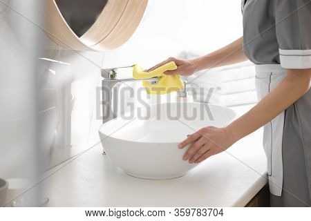 Young Chambermaid Cleaning Tap In Bathroom, Closeup