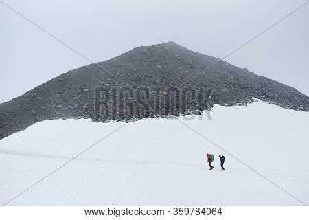 Beautiful View Of Winter Rocky Mountains With Two Male Travelers. Mountaineers With Backpacks Walkin