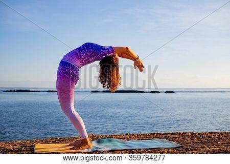 Young Woman Practicing Yoga, Standing In Hasta Uttanasana Pose, Deflection Back. Sunrise Yoga Practi