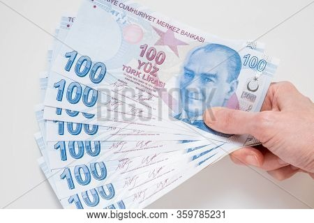 Female Hand Holding A Bunch Of 100 Turkish Lira (try) Banknotes Isolated On White Background.