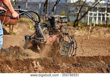 Man Working In The Garden With Garden Tiller.
